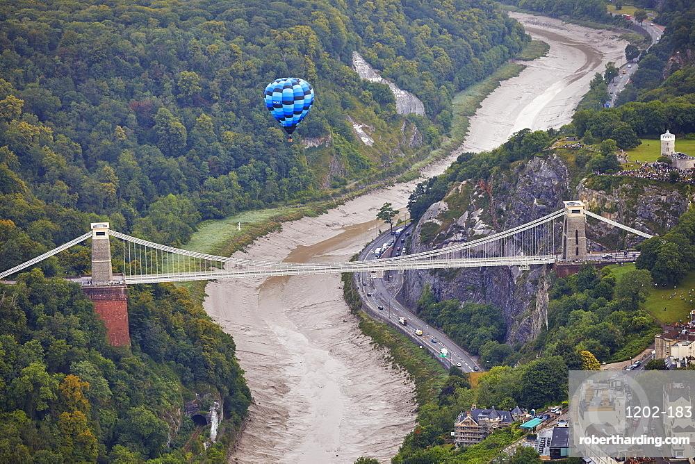 A hot-air balloon flying over Clifton Suspension Bridge, an icon of Bristol, during the Bristol International Balloon Fiesta, Bristol, England, United Kingdom, Europe