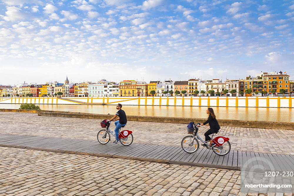 People cycling by the river Rio Guadalquivir, with Triana district in the background, Seville, Andalusia, Spain, Europe