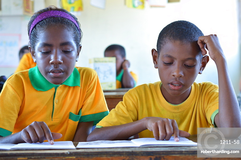 Two grade 3 students reading at Kusbau School in the coastal region of Madang in Papua New Guinea, Pacific