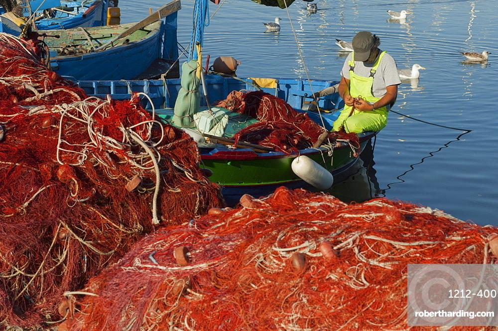 Fisherman mending nets, Alghero, Sardinia, Europe