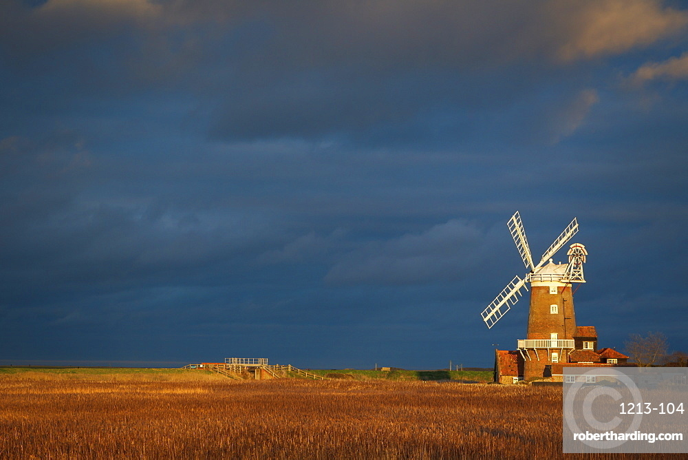 Storm clouds move in over the reedbeds towards Cley Windmill at Cley Next the Sea, Norfolk, England, United Kingdom, Europe