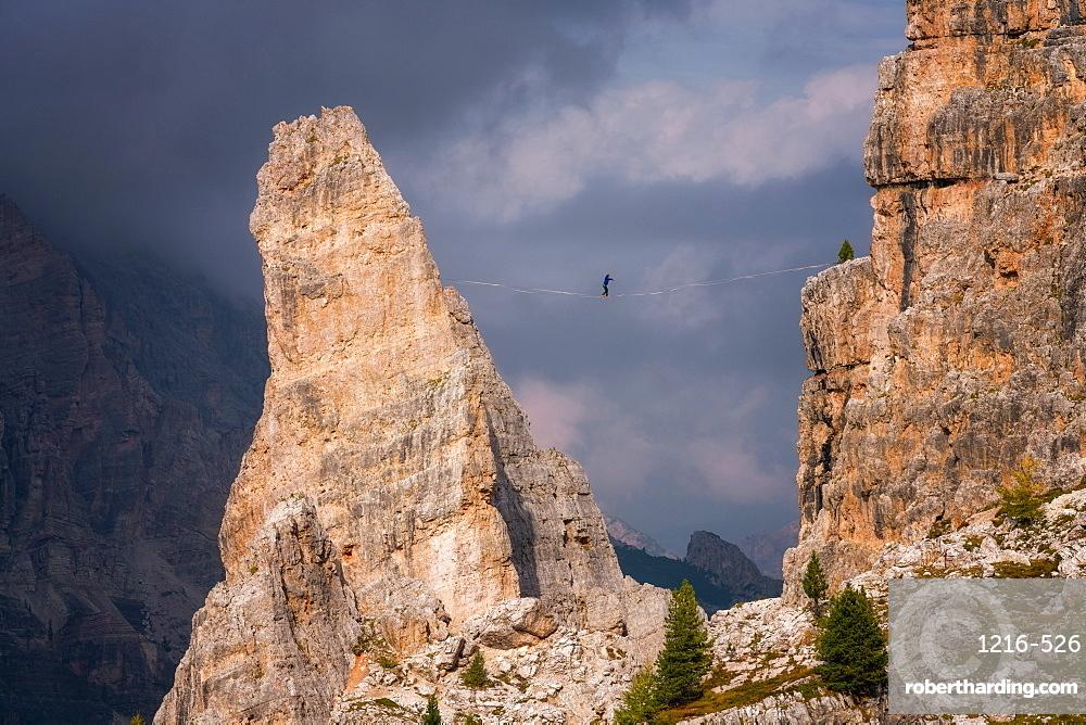 Adventure seeker high wire walking in Cinque Torri, Dolomites, Italy, Europe