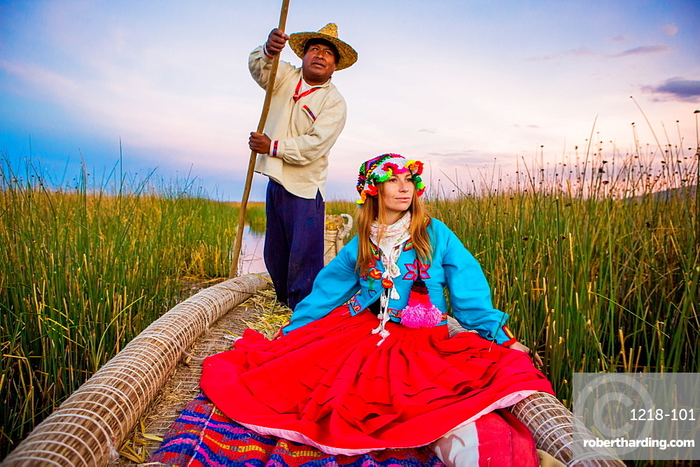 Girl on grass boat with Quechua Indian rower, Floating Grass islands of Uros, Lake Titicaca, Peru, South America