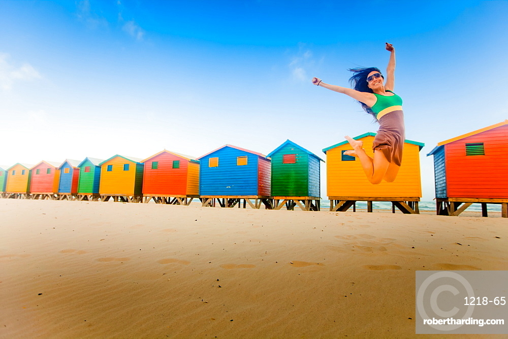 Laura Grier jumping in front of colorful beach huts, Muizenberg Beach, Cape Town, South Africa, Africa