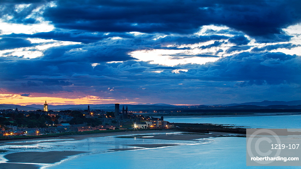 Looking across the bay to St. Andrews harbour and pier with the sun setting beyond the city as dusk falls, St. Andrews, Fife, Scotland, United Kingdom, Europe