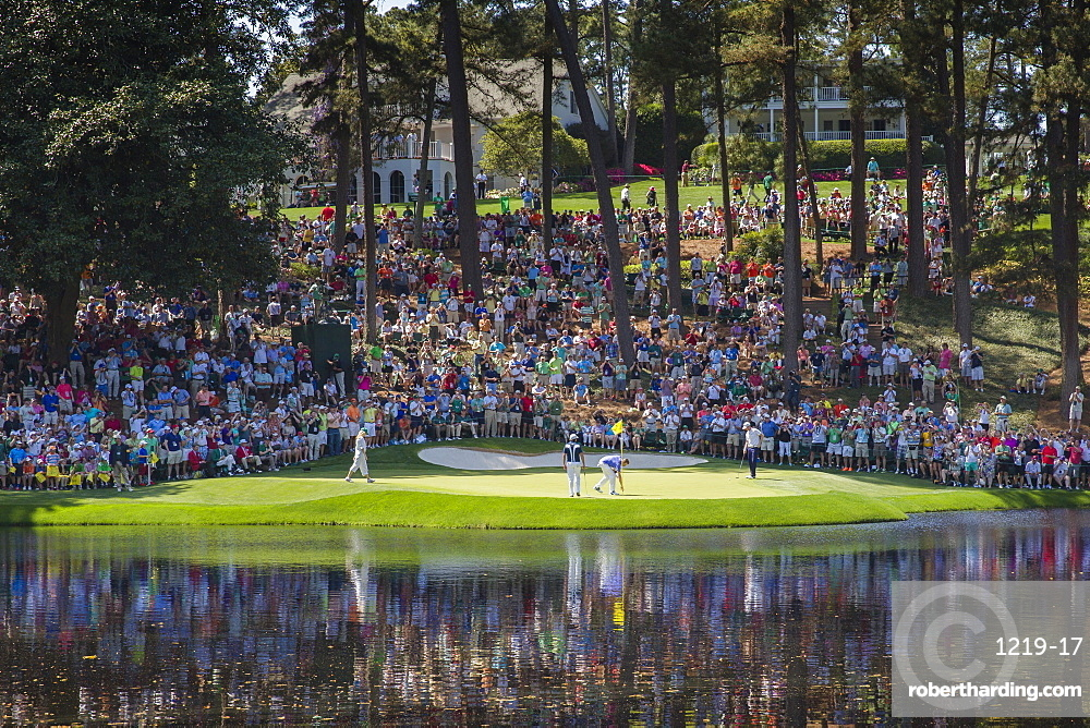 Spectators fill the hill behind the 9th green of the Par 3 course as players finish their round at Augusta National Golf Club, Augusta, Georgia, United States of America, North America