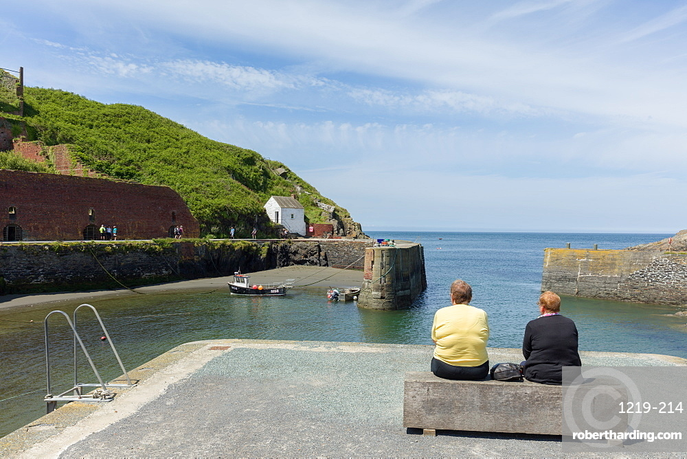 Two ladies on a bench at Porthgain harbour as the Pembrokeshire coast path extends up the cliffs beyond, Wales, United Kingdom, Europe