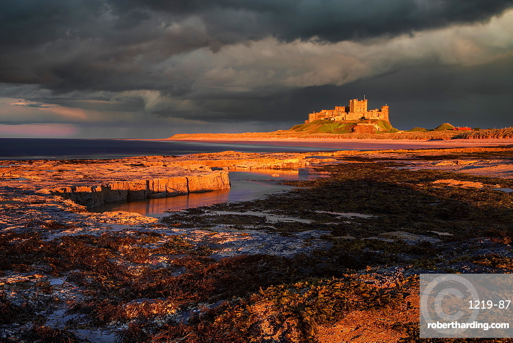 A storm passes behind Bamburgh Castle with the last light of the day illuminating the rocky shoreline and castle, Northumberland, England, United Kingdom, Europe