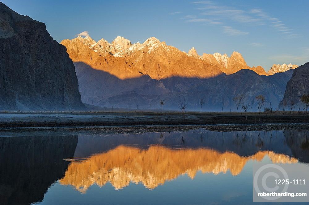 The crystal clear Shyok River creates a mirror image of sunrise on Karakoram peaks beyond the Khapalu valley near Skardu, Gilgit-Baltistan, Pakistan, Asia
