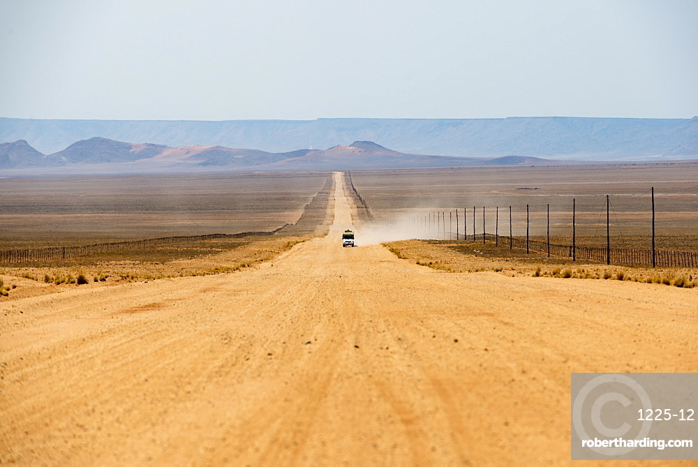 A jeep on a long sandy road in southern Namibia leaves a trail of dust, Namibia, Africa