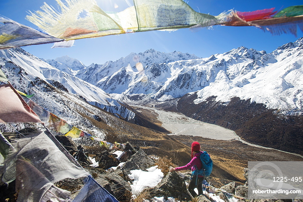 A woman trekking in the Langtang valley in Nepal stands on the top of Kyanjin Ri and looks out towards Ganchempo in the distance, Langtang Region, Himalayas, Nepal, Asia