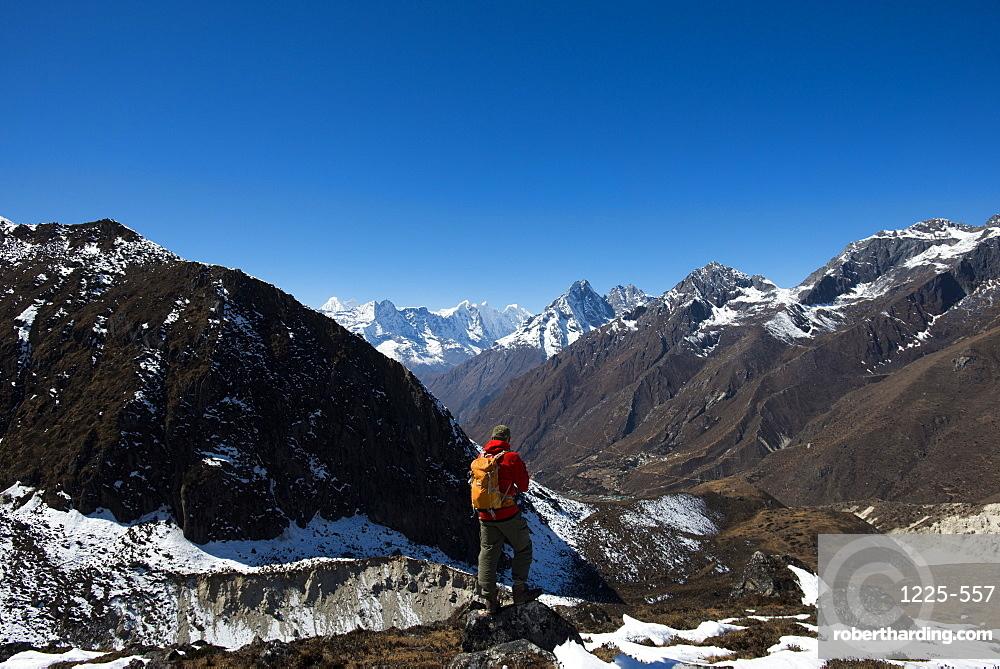A trekker in the Everest region looks down on the Khumbu Valley towards Pangboche, Khumbu Region, Himalayas, Nepal, Asia