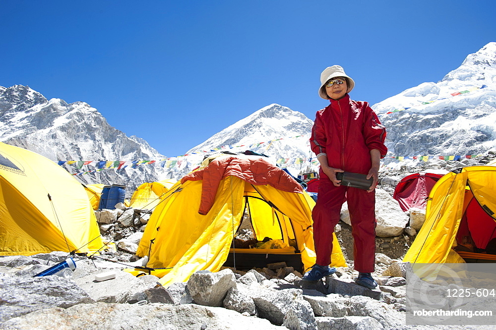 A woman stands by her tent shortly after climbing Everest, Khumbu Region, Himalayas, Nepal, Asia