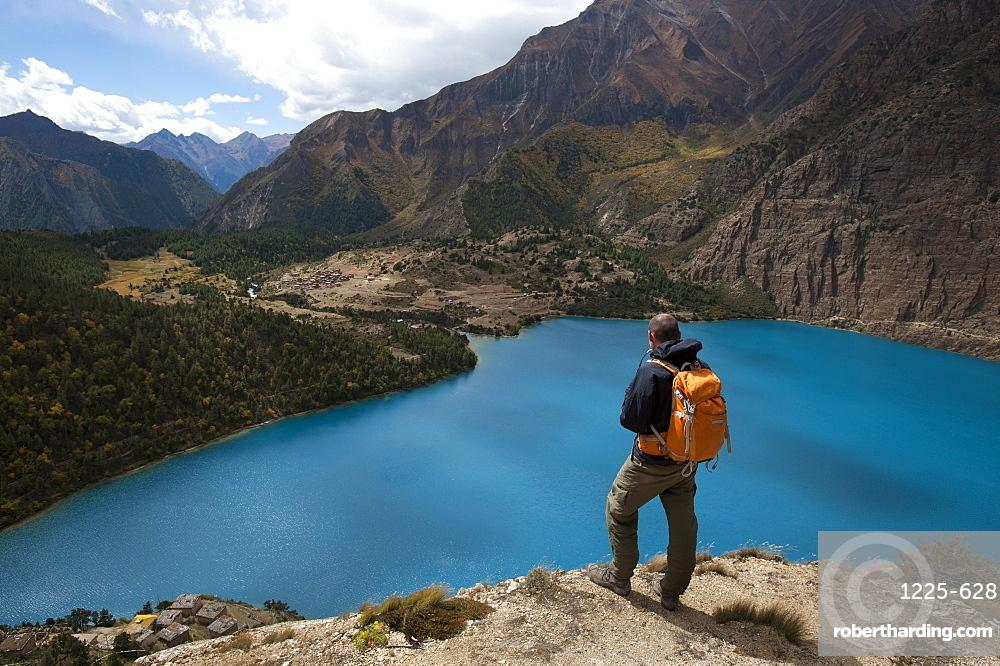 A trekker looks out at the turquoise blue Phoksundo Lake, Dolpa Region, Himalayas, Nepal, Asia