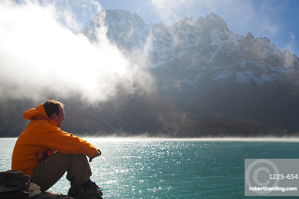 A trekker in the Everest region looks out over Gokyo Lake, Khumbu Region, Nepal, Asia