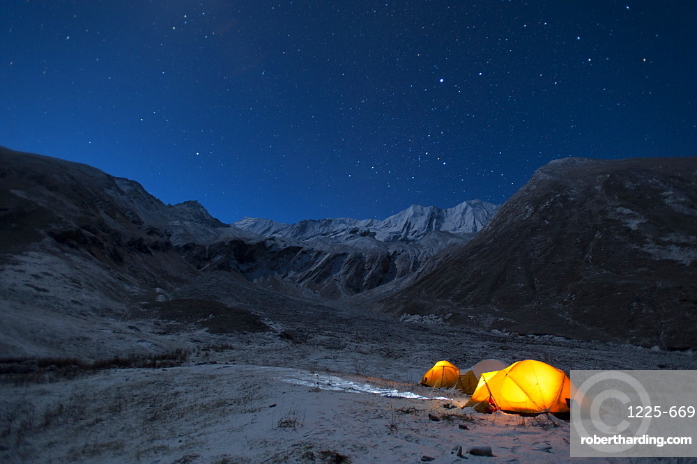 In the little explored Juphal valley in the remote Dolpa region, a man stands outside his tent on a cold night, Dolpa, Himalayas, Nepal, Asia