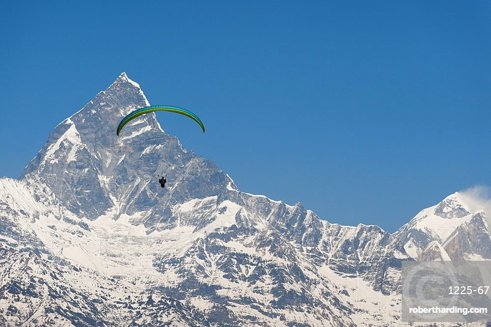 A paraglider hangs in the air with the dramatic peak of Machapuchare (Fishtail mountain) in the distance, Himalayas, Nepal, Asia