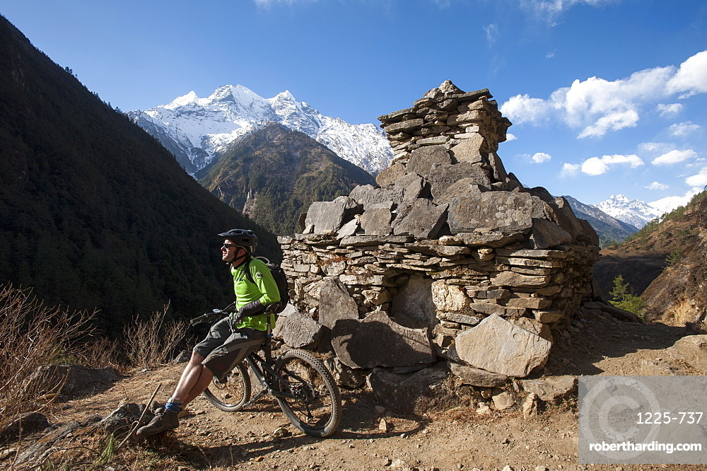 A mountain biker in the Tsum Valley stops to check out the view, Nepal, Asia