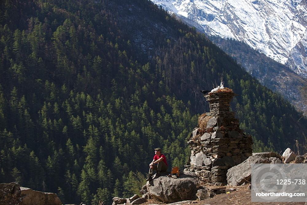 A trekker stops by a chorten in the Tsum Valley, Nepal, Asia