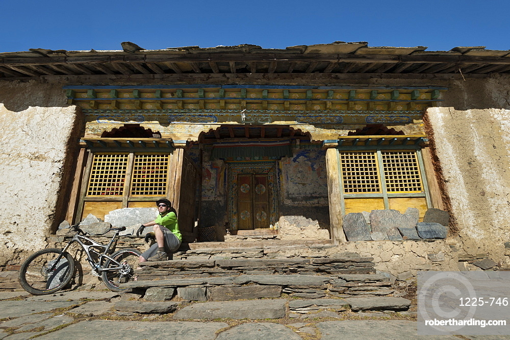 A mountain biker takes a well earned rest at Mu Gompa, the last village in the Tsum Valley, Nepal, Asia