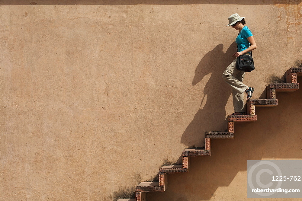 A tourist climbs downs some exposed steps within the Fatehpur Sikri temple complex, Uttar Pradesh, India, Asia