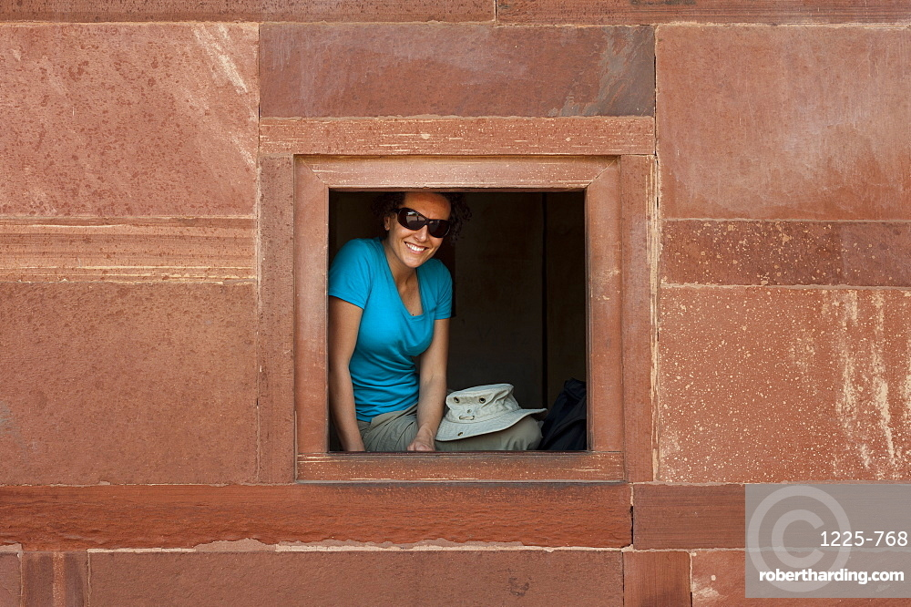 A tourist peeks out from one the windows within the Fatehpur Sikri temple complex, Uttar Pradesh, India, Asia