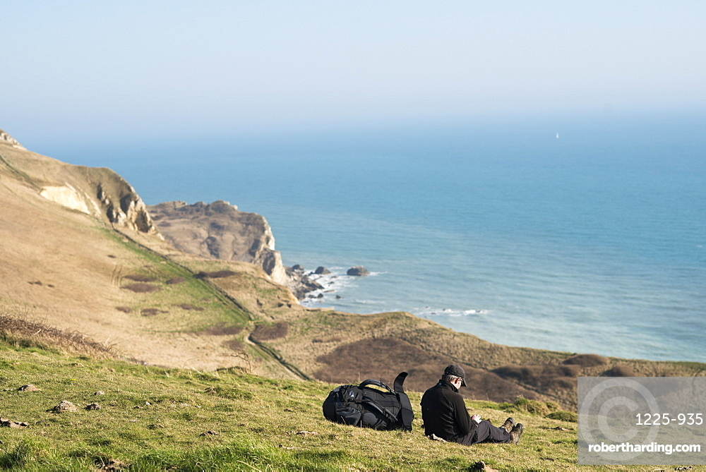 A man takes a break from a coastal walk near Lulworth Cove in Dorset, Jurassic Coast, UNESCO World Heritage Site, England, United Kingdom, Europe