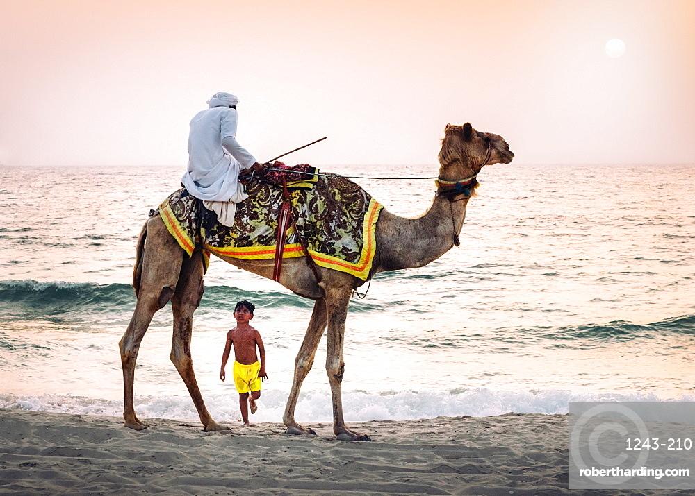 Boy stares in amazement at Arabic man wearing a thawb riding a camel on a beach, Dubai, United Arab Emirates, Middle East