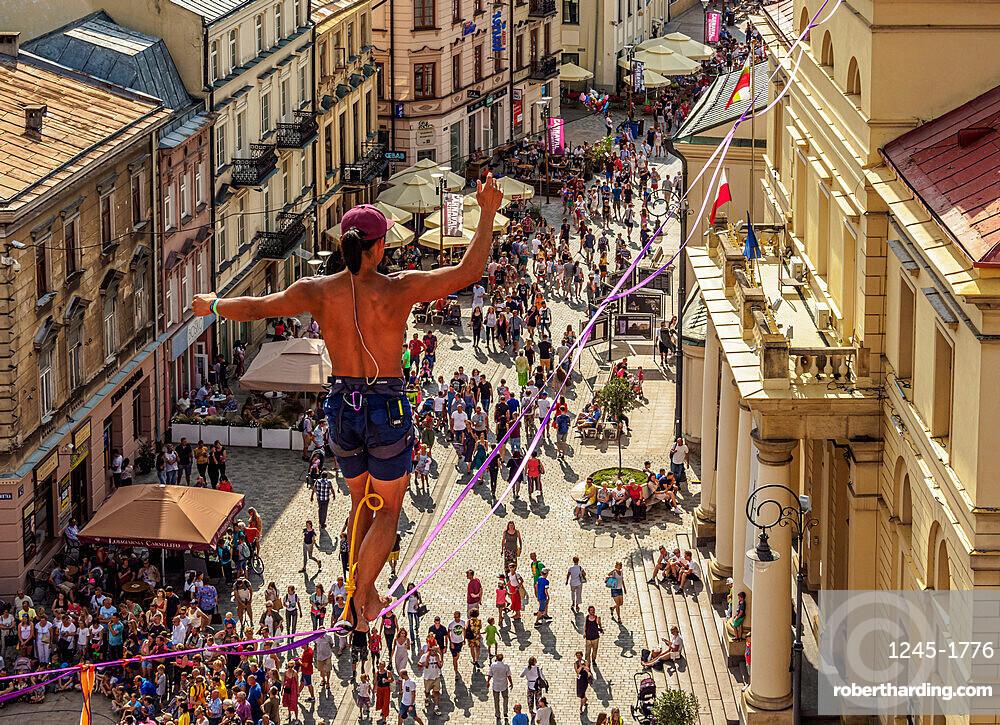 Man highlining with City Hall and Krakowskie Przedmiescie Promenade in the background, Urban Highline Festival, Lublin, Poland