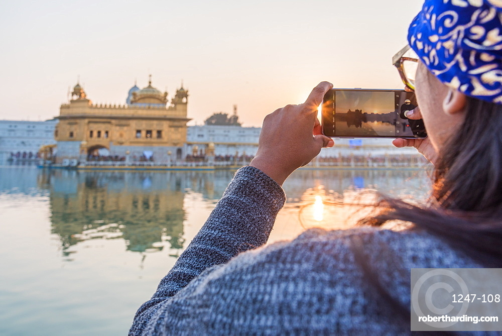 An Indian lady takes a smartphone picture of the Golden Temple at sunset, The Golden Temple, Amritsar, Punjab, India, Asia