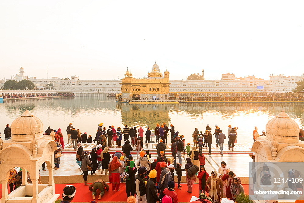 Crowds gather to pray and watch the sunset at The Golden Temple, Amritsar, Punjab, India, Asia