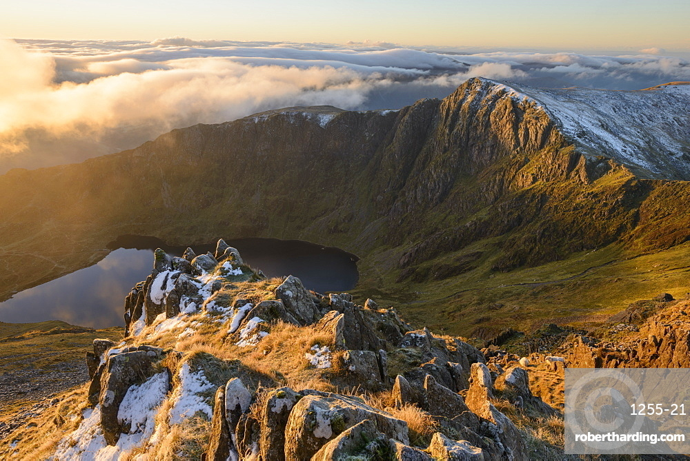 Morning light illuminates the top of Craig Cau during a cloud inversion, photographed from the top of Cadair Idris, Snowdonia.