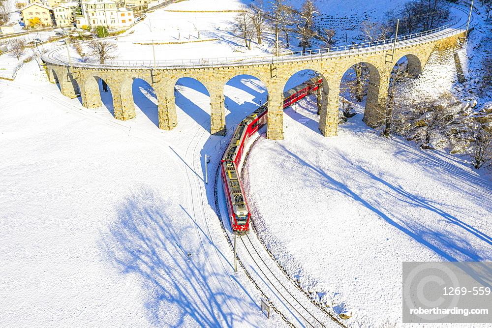 Bernina Express passes under the helical (spiral) viaduct of Brusio, UNESCO World Heritage Site, Valposchiavo, Canton of Graubunden, Switzerland, Europe
