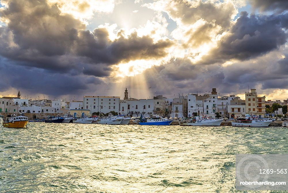 Old town illuminated by sun rays that filters between clouds, Monopoli, Apulia, Italy, Europe