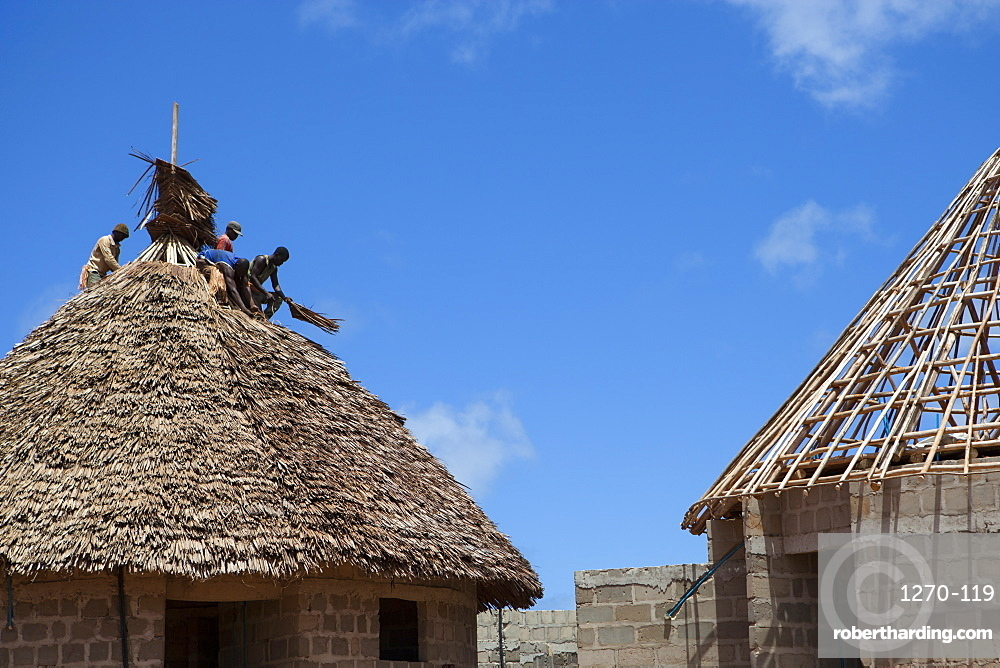 Men thatching the roof of a new house, Tanzania, East Africa, Africa