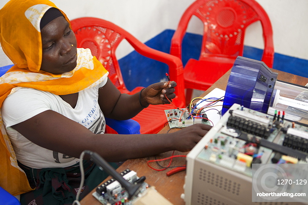 A female solar engineer, known as a solar mama, works on the printed circuit board of a solar lamp, Tanzania, East Africa, Africa