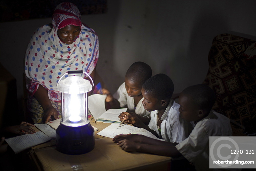 A group of boys read their homework by the light of a solar lantern, Tanzania, East Africa, Africa