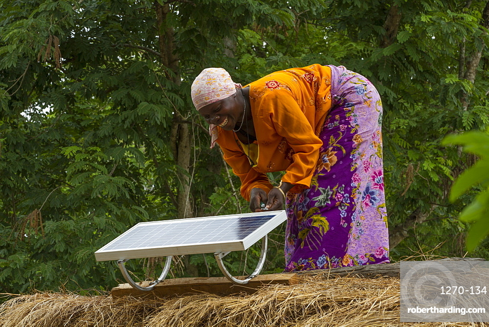 A woman, known as a Solar Mama, fixes a solar panel to the top of a traditional thatched mud hut, Tanzania, East Africa, Africa