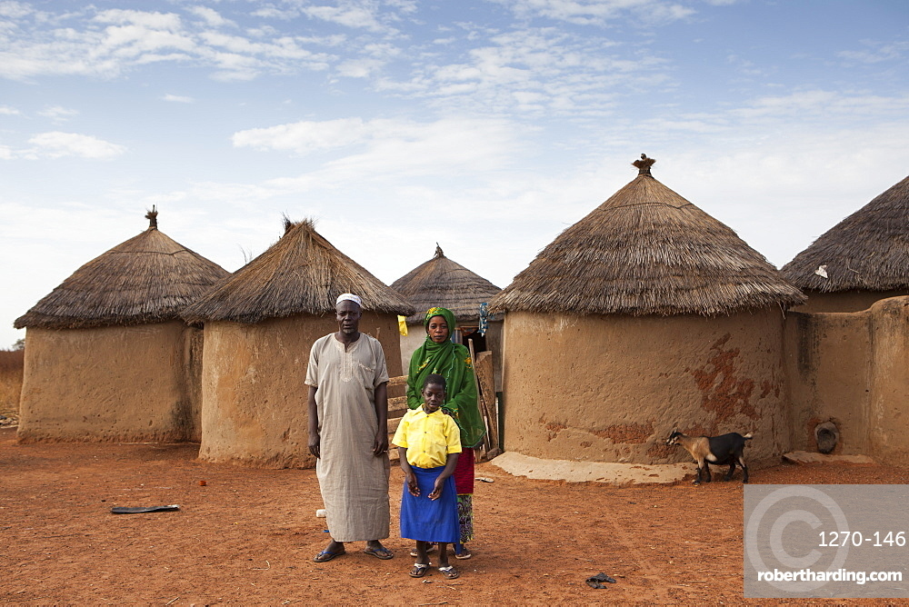 A young school girl with her parents outside their home in Tinguri, northern Ghana, West Africa, Africa