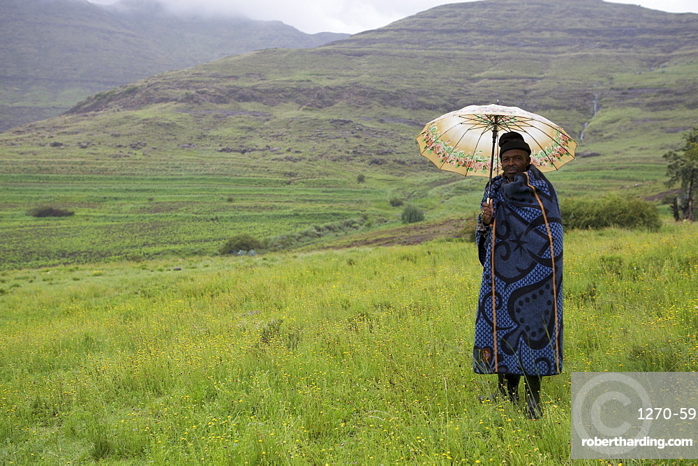 A man holding an umbrella and wrapped in a blue blanket stands in the mountains, Lesotho, Africa