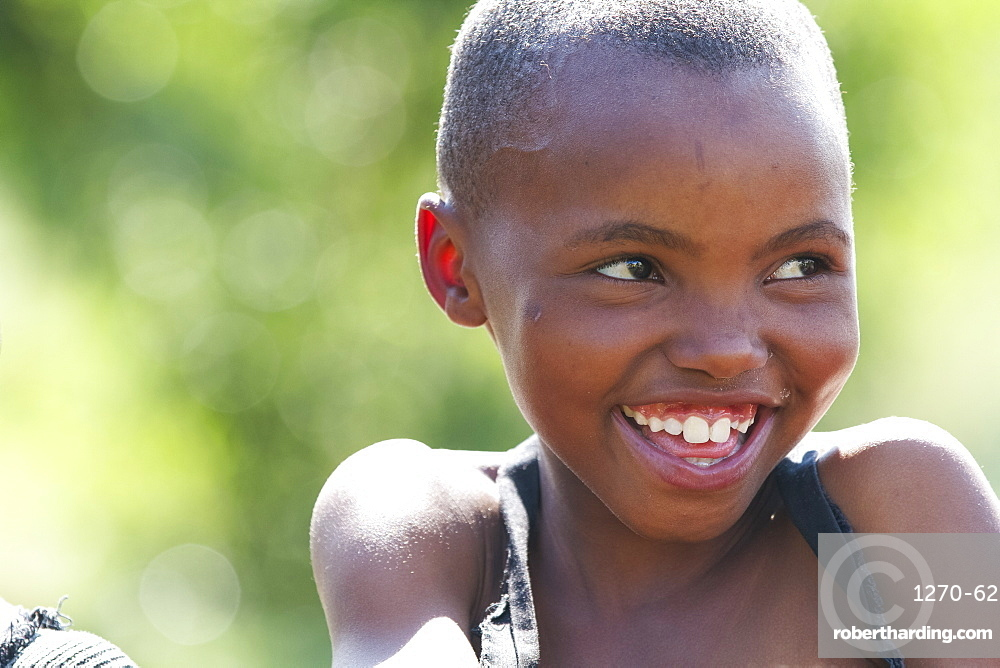 A young girl smiling and looking off to the right, Lesotho, Africa