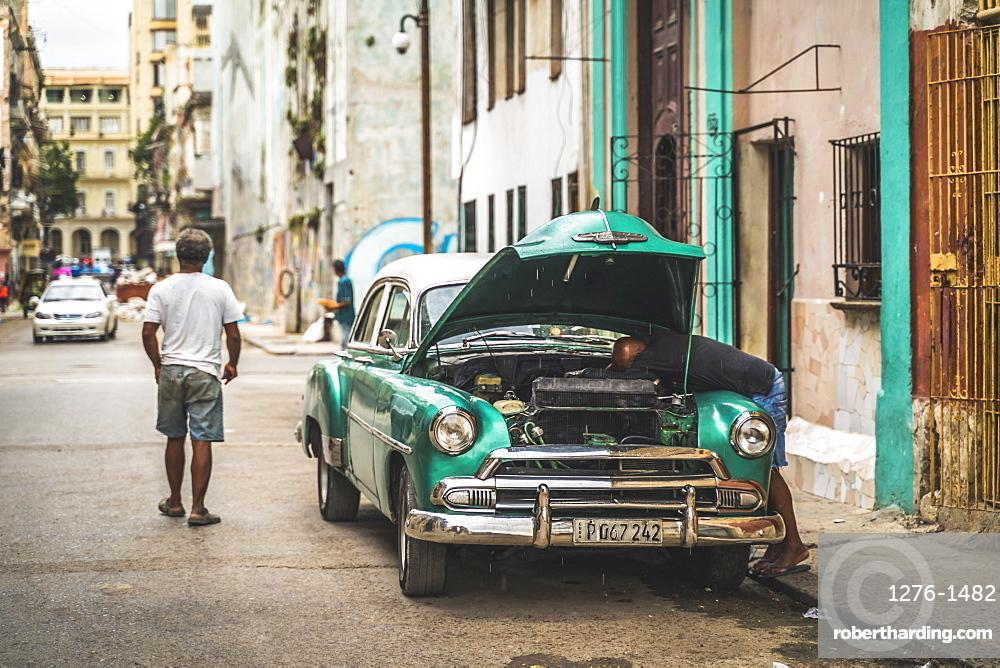 Local fixing his broken down American vintage car, La Habana (Havana), Cuba, West Indies, Caribbean, Central America