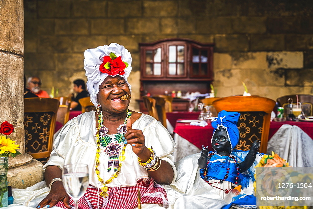 Cuban woman posing for photos while smoking big Cuban cigar in La Habana, (Havana), Cuba, West Indies, Caribbean, Central America