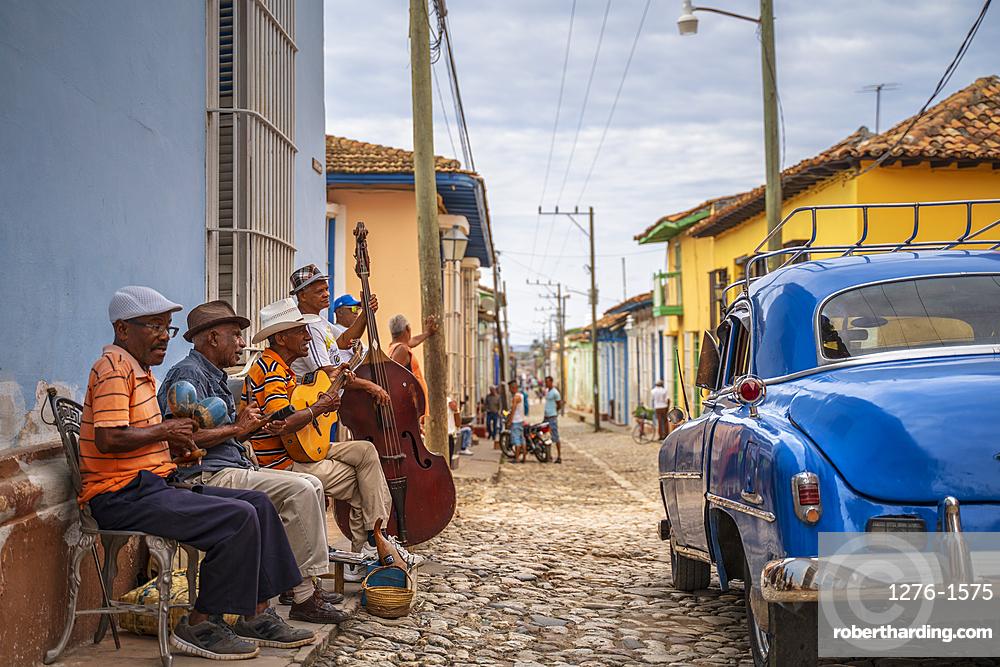 Elderly Cubans playing music on the street, American classic car, Trinidad, Sancti Spiritus Province, Cuba, West Indies, Caribbean, Central America