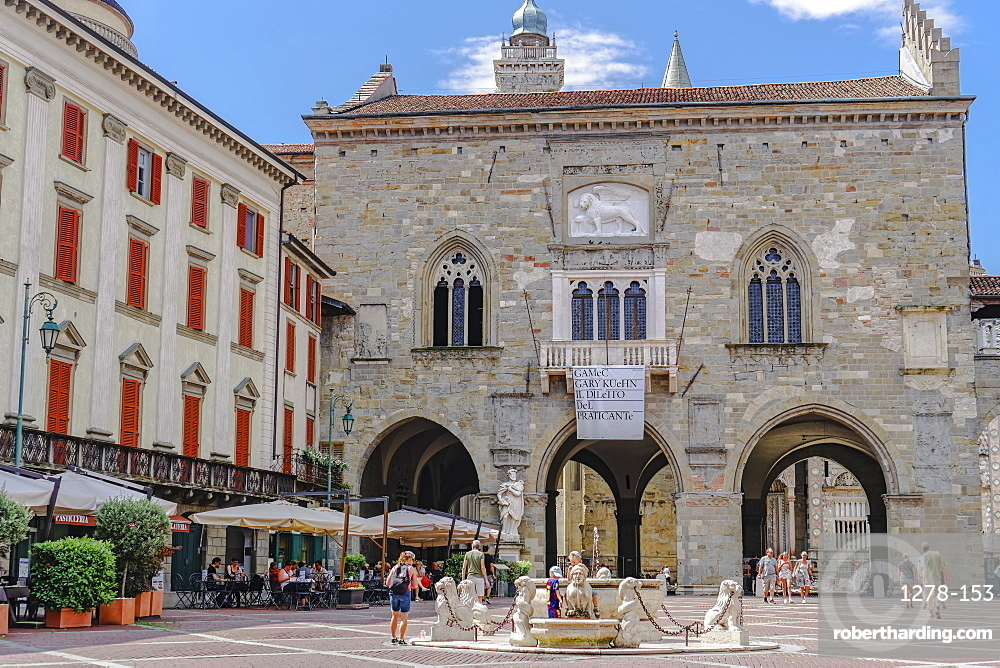 Old Town Palace (Palazzo della Ragione) on Piazza Vecchia with fountain and crowd in Citta Alta, Bergamo, Lombardy, Italy, Europe
