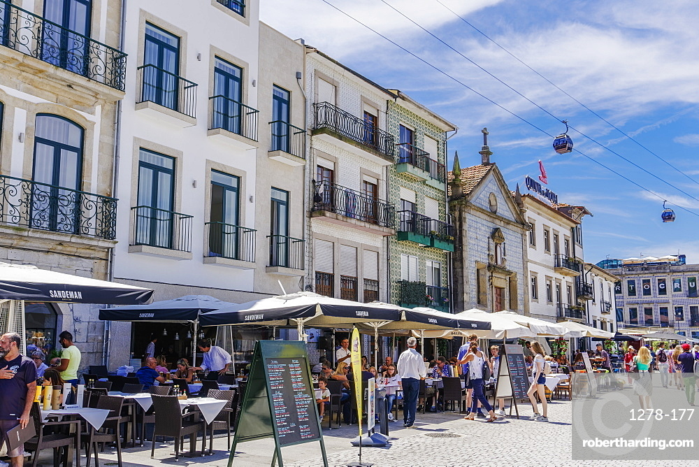 Day view of food shops with outdoor seats by Douro River waterfront and buildings, Vila Nova de Gaia, Porto, Portugal, Europe