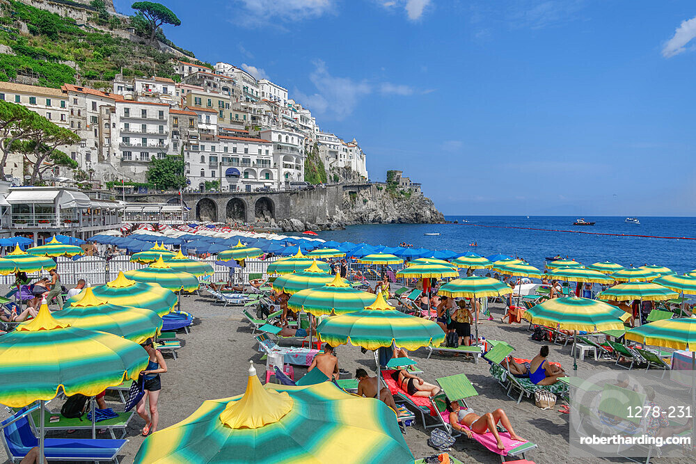 Amalfi Town, Italy daily beach view with bathers and colorful umbrellas before low rise buildings in Costiera Amalfitana.