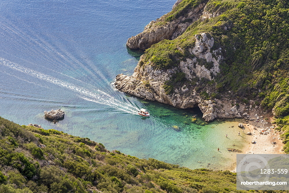 High-angle view down to one of the Porto Timoni beaches and a taxi boat approaching the bay, Afionas, Corfu, Greek Islands, Greece, Europe