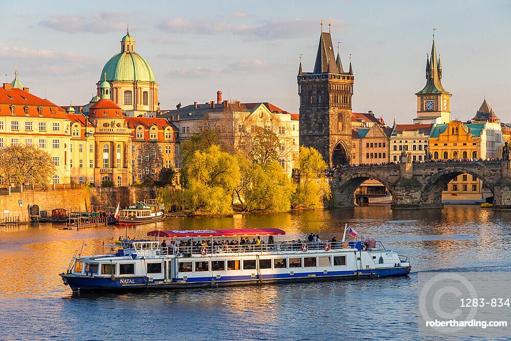 Tourist boat passing Charles Bridge and the Old Town Bridge Tower on Vltava River, Prague, Bohemia, Czech Republic, Europe