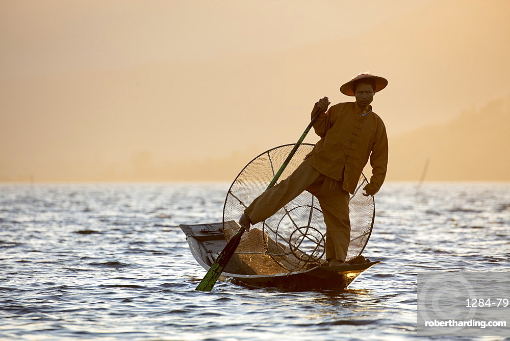 A fisherman rowing with one leg at sunset on Inle Lake, Shan State, Myanmar (Burma), Asia